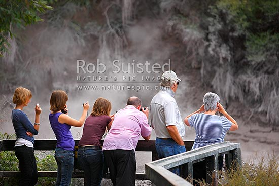Tourist visitors viewing boiling geothermal mudpools, steam and hotpools, Rotorua, Rotorua District, Bay of Plenty Region, New Zealand (NZ) stock photo.