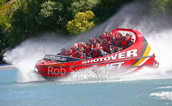 Shotover Jet jetboat carrying tourists on the Shotover River. A popular Queenstown attraction. 360 degree spin, Queenstown, Queenstown Lakes District, Otago Region, New Zealand (NZ) stock photo.