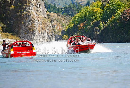 Shotover Jet jetboat carrying tourists on the Shotover River. A popular Queenstown attraction, Queenstown, Queenstown Lakes District, Otago Region, New Zealand (NZ) stock photo.