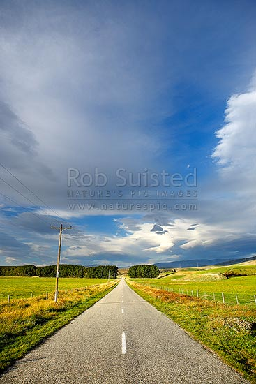 Rural country road, powerlines and farmland with moody cloudy sky above just before southerly storm front, Bendigo, Central Otago District, Otago Region, New Zealand (NZ) stock photo.