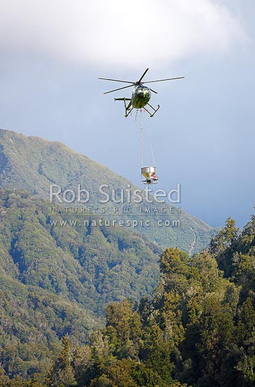 Helicopter with underslung aerial bait application bucket hopper used for aerial 1080 poison operations against possums. Hughes 500 helicopter, New Zealand (NZ) stock photo.
