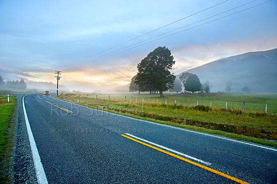 Early morning mists drifting across the road as shafts of sunlight appear from the dawn. Car on State Highway 63, St Arnaud, Tasman District, Tasman Region, New Zealand (NZ) stock photo.