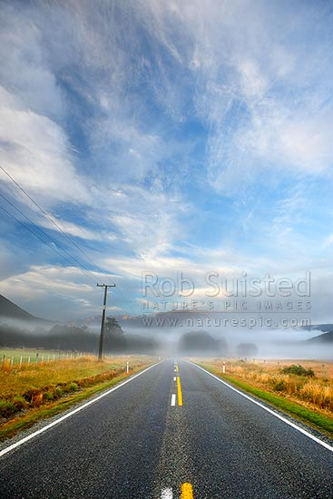 Early morning mists drifting across the road with mountains beyond. State Highway 63, St Arnaud, Tasman District, Tasman Region, New Zealand (NZ) stock photo.