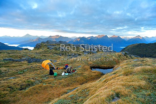 Tramper preparing food for breakfast at sunrise. Alpine tent camp next to mountain tarn, high on the Thomas Range. Southern Alps and Mount Brewster (left), Haast, Westland District, West Coast Region, New Zealand (NZ) stock photo.