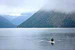 Lone rower on misty lake