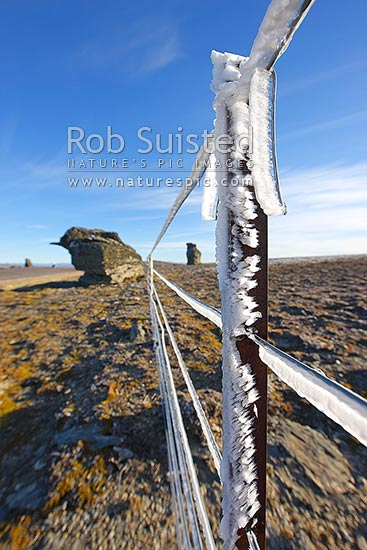 High country farm fenceline wires encrusted with ice from freezing cloud and frost. Old Man Range in autumn. 1600 metres high. Rock tors, Alexandra, Central Otago District, Otago Region, New Zealand (NZ) stock photo.