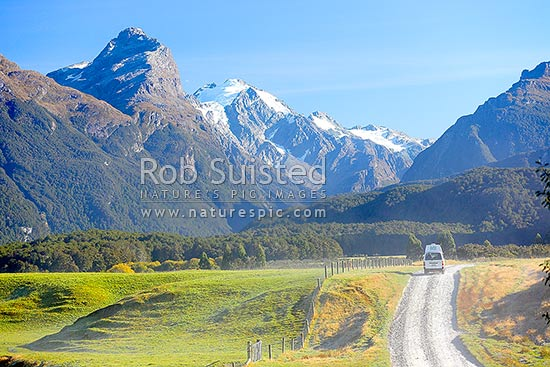 Campervan, frosty morning farmland and gravel road below Mt Chaos (1995m left) and Poseidon Peak (2208m - snowy). Dart River valley at Paradise, Paradise, Glenorchy, Queenstown Lakes District, Otago Region, New Zealand (NZ) stock photo.