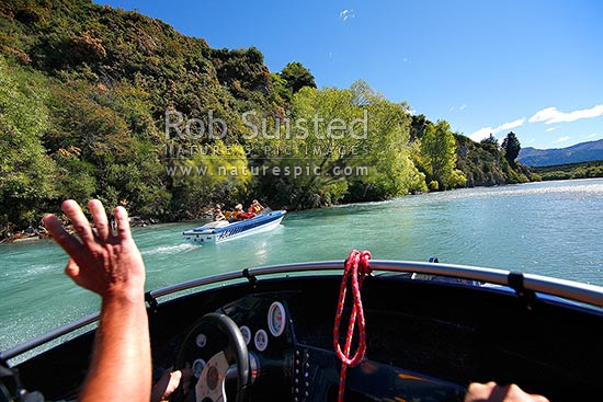 Jetboating on the lower Shotover River, passing and waving to another jetboat, Queenstown, Queenstown Lakes District, Otago Region, New Zealand (NZ) stock photo.
