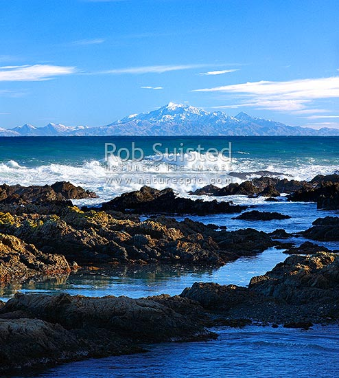 Wild Wellington south coast. Waves rolling in from Cook Strait with snow covered Inland Kaikoura Mountain Ranges beyond. Rockpools in foreground, Wellington, Wellington City District, Wellington Region, New Zealand (NZ) stock photo.
