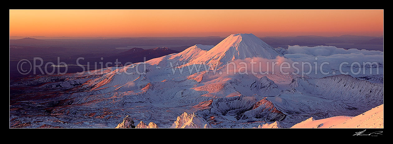 Image of Mount Ngauruhoe sunset (2287m) from near summit of Mt Ruapehu. Pinnacle Ridge in foreground. Mt Tongariro (1967m) and Lake Taupo behind. Heavy winter snow. Panorama, Tongariro National Park, Ruapehu District, Manawatu-Wanganui Region, New Zealand (NZ) stock photo image