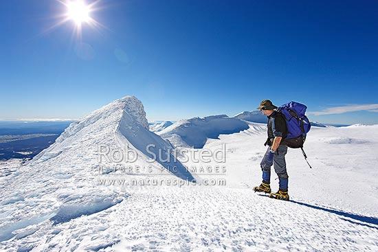 tramper climbing along icy ridge above summit plateau of