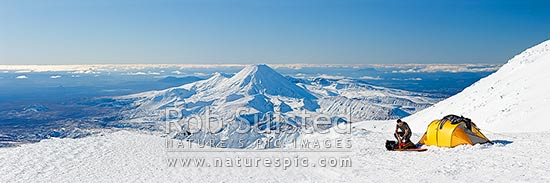 Mount Ngauruhoe (2287m) from near summit of Mt Ruapehu. Pinnacle Ridge in foreground centre with Mt Tongariro (1967m) beyond. Climber packing up alpine tent camp in heavy winter snow. Panorama, Tongariro National Park, Ruapehu District, Manawatu-Wanganui Region, New Zealand (NZ) stock photo.