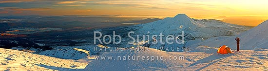 Mount Ngauruhoe sunrise (2287m) from alpine tent camp near summit of Mt Ruapehu. Mt Tongariro (1967m) and Lake Taupo behind. Heavy winter snow. Panorama, Tongariro National Park, Ruapehu District, Manawatu-Wanganui Region, New Zealand (NZ) stock photo.
