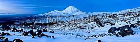 Mount Ngauruhoe (2287m), distinctive volcanic cone in Tongariro National Park with Mt Tongariro (1967m) to left, panorama seen from Whakapapa in winter snow at twilight, Tongariro National Park, Ruapehu District, Manawatu-Wanganui Region, New Zealand (NZ) stock photo.