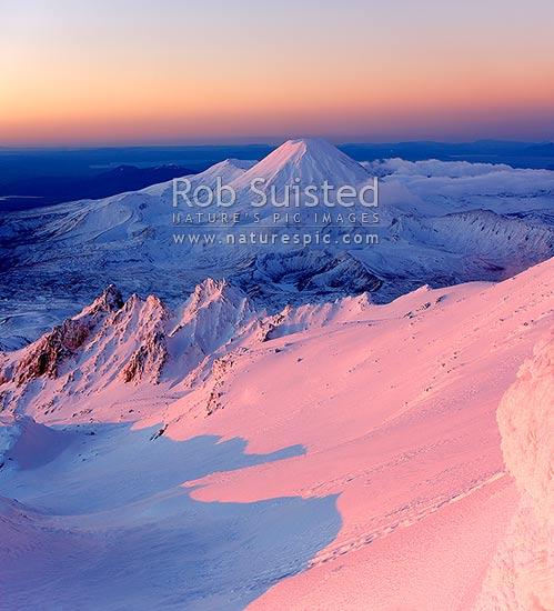 Mount Ngauruhoe sunset (2287m) from near summit of Mt Ruapehu. Pinnacle Ridge in foreground. Mt Tongariro (1967m) and Lake Taupo behind. Heavy winter snow, Tongariro National Park, Ruapehu District, Manawatu-Wanganui Region, New Zealand (NZ) stock photo.