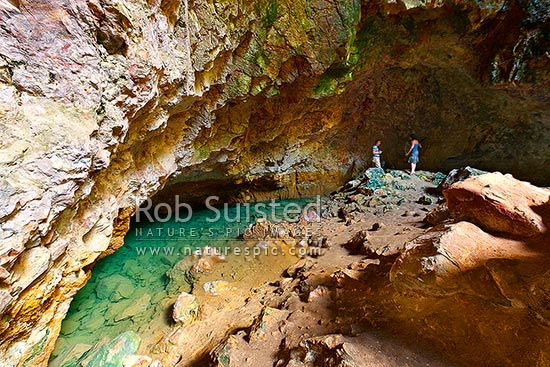 Visitors viewing the geothermally active pool in Ruatapu Cave at Orakei Korako cave and thermal park, Lake Ohakuri, Rotorua, Rotorua District, Bay of Plenty Region, New Zealand (NZ) stock photo.