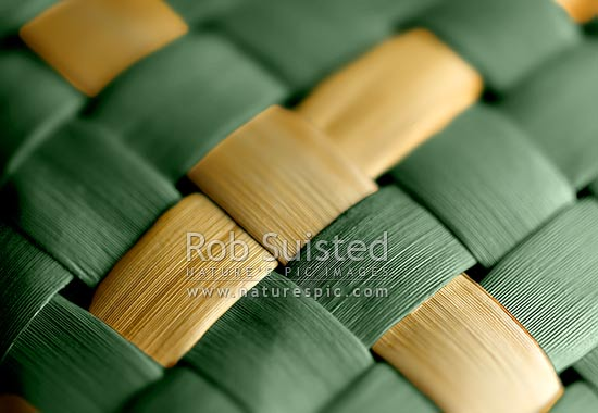 Traditional indigenous Maori weaving of flax leaves and fibre (Phormium sp. Harakeke). Criss cross pattern. Yellow and green coloured, New Zealand (NZ) stock photo.