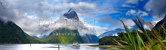 Milford Sound Panorama in clearing weather, Fiordland National Park. Small boat below Mitre Peak (1683m) entering Freshwater Basin. Sinbad Gully valley left., Milford Sound, Fiordland National Park, Southland District, Southland Region, New Zealand (NZ) stock photo.