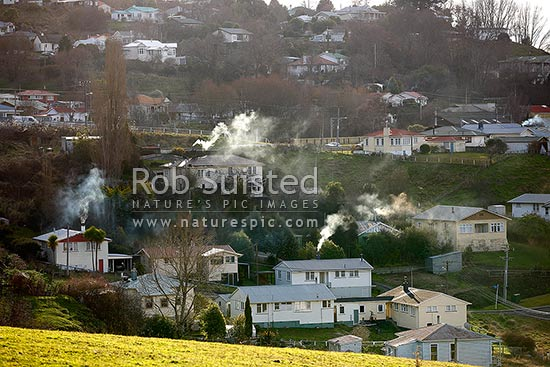 Taihape houses with wood fires for home heating on cold mid winter afternoon. Household chimney smoke air pollution, Taihape, Rangitikei District, Manawatu-Wanganui Region, New Zealand (NZ) stock photo.
