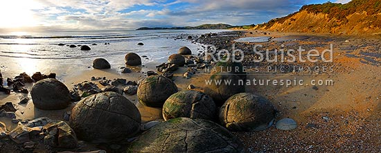 Moeraki Boulders / Kaihinaki on Koekohe Beach. 60 Million year old mudstone concretions. Moeraki Township beyond. Panorama, Moeraki, Waitaki District, Otago Region, New Zealand (NZ) stock photo.