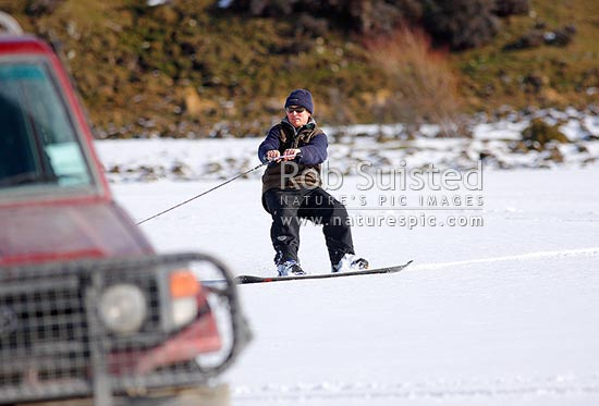 Winter fun on the farm. Snowboarding in paddocks towed behind the Landcruiser 4x4. Glenthorne Station, Lake Coleridge, Selwyn District, Canterbury Region, New Zealand (NZ) stock photo.