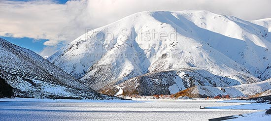Lake Lyndon with Torlesse Range beyond in heavy winter snowfall. Trout flyfisherman fishing on shoreline. Panorama, Porters Pass, Selwyn District, Canterbury Region, New Zealand (NZ) stock photo.