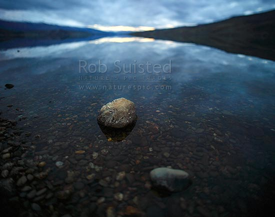 Lake Dunstan shores at Cromwell on a moody calm evening, Cromwell, Central Otago District, Otago Region, New Zealand (NZ) stock photo.