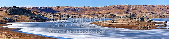 Poolburn reservior frozen in winter. Fishing baches and cribs around edge. Lord of the Rings location Rohan. Panorama, Ida Burn Valley, Central Otago District, Otago Region, New Zealand (NZ) stock photo.