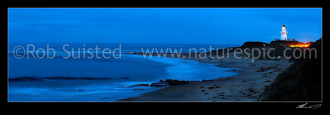 Image of Waipapa Point lighthouse and beach panorama on a moody evening. Car headlights near lighthouse, Fortrose, Southland District, Southland Region, New Zealand (NZ) stock photo image