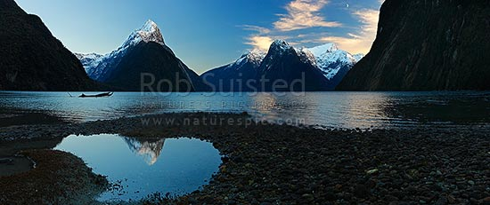 Mitre Peak reflecting in Milford Sound Fiordland. Mitre Peak left (1683m), The Lion (1302m) and Mt Pembroke (2015m) centre right. Panorama at dawn with moon, Milford Sound, Fiordland National Park, Southland District, Southland Region, New Zealand (NZ) stock photo.