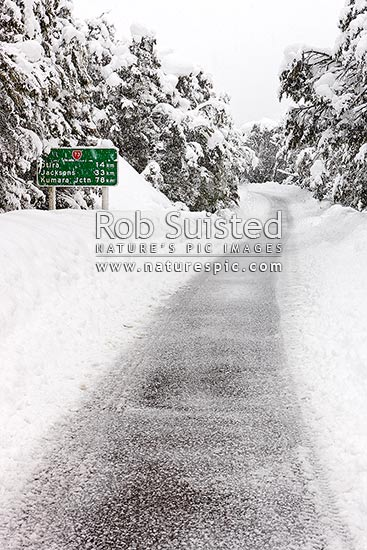 Arthur's Pass State Highway 73 to West Coast in heavy winter snow. Hazardous driving conditions. Snowing and road limited to one lane. Road signs, Arthur's Pass National Park, Selwyn District, Canterbury Region, New Zealand (NZ) stock photo.