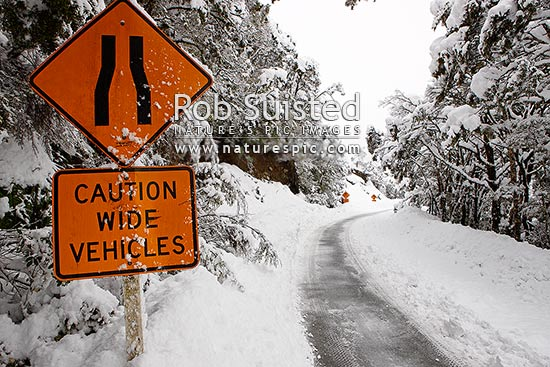 Arthur's Pass State Highway 73 to West Coast in heavy winter snow. Hazardous driving conditions. Snowing and road limited to one lane. Caution Wide Vehicles road sign, Arthur's Pass National Park, Selwyn District, Canterbury Region, New Zealand (NZ) stock photo.