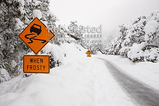 Arthur's Pass State Highway 73 to West Coast in heavy winter snow. Hazardous driving conditions. Snowing and road limited to one lane. Caution slippery when frosty road sign, Arthur's Pass National Park, Selwyn District, Canterbury Region, New Zealand (NZ) stock photo.