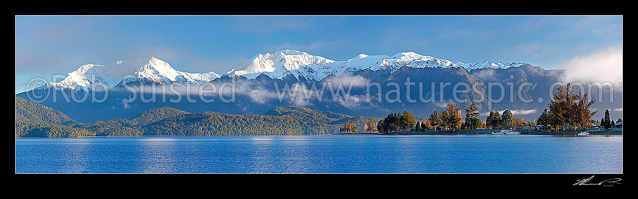 Image of Lake Te Anau and Te Anau township, with winter snow capped Murchison Mountains and Fiordland National Park beyond. Early morning panorama, Te Anau, Southland District, Southland Region, New Zealand (NZ) stock photo image