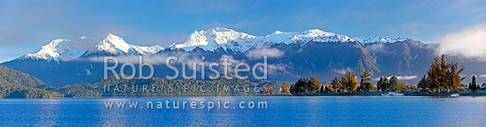 Lake Te Anau and Te Anau township, with winter snow capped Murchison Mountains and Fiordland National Park beyond. Early morning panorama, Te Anau, Southland District, Southland Region, New Zealand (NZ) stock photo.