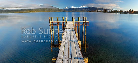 Lake Te Anau and lakeside jetty, with winter snow capped Murchison Mountains and Fiordland National Park beyond. Calm early morning panorama, Te Anau, Southland District, Southland Region, New Zealand (NZ) stock photo.