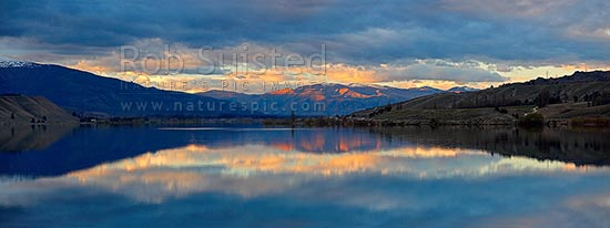 Lake Dunstan sunset looking north from Deadmans Point, past Quartz Reef Point to high country, Cromwell, Central Otago District, Otago Region, New Zealand (NZ) stock photo.