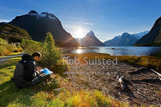 Milford Sound with independent tourist traveller or backpacker reading a book and enjoying a coffee in the sun in front of Mitre Peak, Fiordland National Park, Southland District, Southland Region, New Zealand (NZ) stock photo.