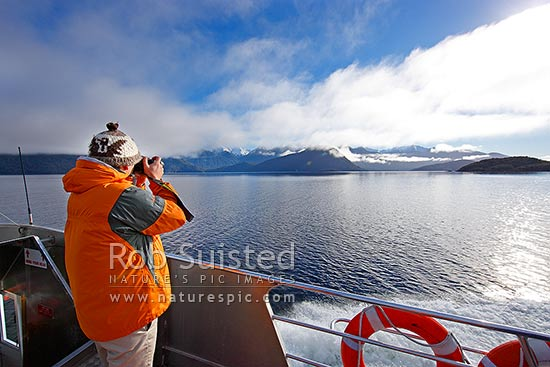 Lake Manapouri boat trip with Real Journeys. Tourist travellers enjoying and photographing the view enroute to Doubtful Sound, Manapouri, Southland District, Southland Region, New Zealand (NZ) stock photo.