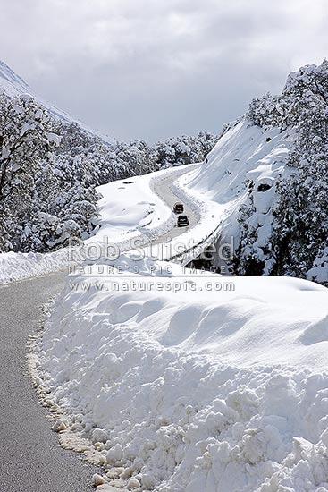 Arthur's Pass State Highway 73 to West Coast in heavy winter snow. Hazardous driving conditions. Road limited to one lane, Arthur's Pass National Park, Selwyn District, Canterbury Region, New Zealand (NZ) stock photo.