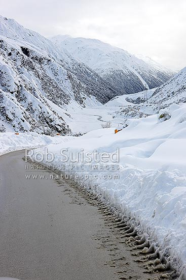 Arthur's Pass State Highway 73 to West Coast in heavy winter snow. Hazardous driving conditions above Otira Gorge. Snowing and road limited to one lane, Arthur's Pass National Park, Selwyn District, Canterbury Region, New Zealand (NZ) stock photo.