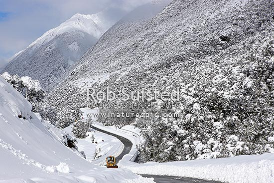 Arthur's Pass State Highway 73 to West Coast in heavy winter snow with grader clearing road. Hazardous driving conditions. Road limited to one lane, Arthur's Pass National Park, Selwyn District, Canterbury Region, New Zealand (NZ) stock photo.