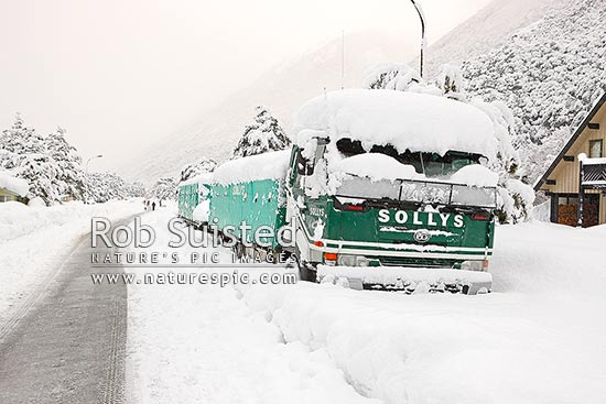 Arthur's Pass State Highway 73 to West Coast in heavy winter snow. Trucks stuck in snow bank in Arthur's Pass Township, Arthur's Pass National Park, Selwyn District, Canterbury Region, New Zealand (NZ) stock photo.