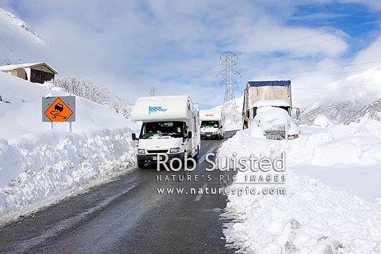 Arthur's Pass State Highway 73 to West Coast in heavy winter snow. Tourist campervans passing trucks stuck in snow bank above Otira Gorge, Arthur's Pass National Park, Selwyn District, Canterbury Region, New Zealand (NZ) stock photo.