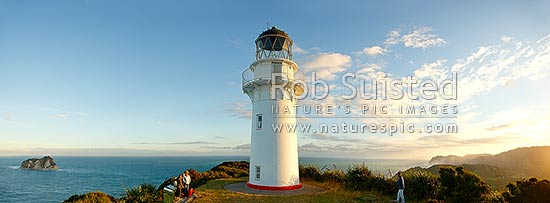 East Cape Lighthouse panorama at dusk with tourist visitors taking photograph. East Island (Whangoakeno) at left, East Cape, Gisborne District, Gisborne Region, New Zealand (NZ) stock photo.