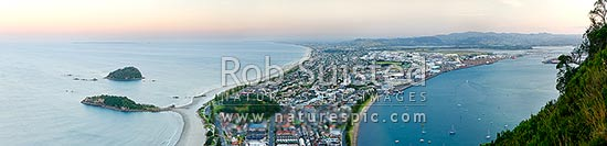 View from Mt Maunganui (232m) Mauao, over beach and Moturiki and Motuotau Islands, towards Papamoa, Tauranga Harbour right. Panorama at dusk, Mount Maunganui, Tauranga District, Bay of Plenty Region, New Zealand (NZ) stock photo.