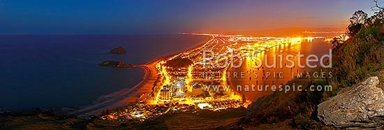 View from Mt Maunganui (232m) over beach and Moturiki and Motuotau Islands, towards Papamoa, night time panorama. Tauranga Harbour right., Mount Maunganui, Tauranga District, Bay of Plenty Region, New Zealand (NZ) stock photo.
