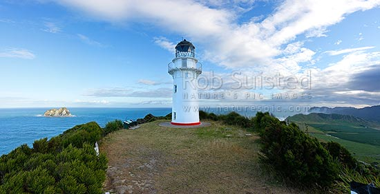 East Cape lighthouse on hill (141m) above East Island (Whangoakeno) left, Waikori Bluff distant right. Panorama, East Cape, Gisborne District, Gisborne Region, New Zealand (NZ) stock photo.