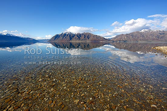 Lake Hawea on a perfect calm spring/winter day reflecting the surrounding snowy ranges. Mirror calm lake surface with ripples and rings, Lake Hawea, Otago, Queenstown Lakes District, Otago Region, New Zealand (NZ) stock photo.