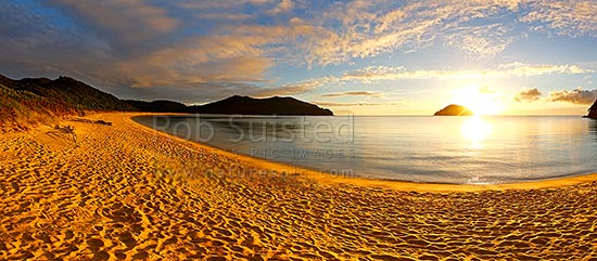 Abel Tasman sunrise at Onetahuti Beach, with Tonga Island and Reef Point (centre) beyond. Tonga Roadstead. Golden sand beach. Panorama, Abel Tasman National Park, Tasman District, Tasman Region, New Zealand (NZ) stock photo.